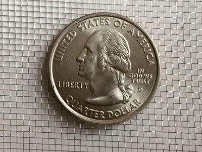 a coin on stainless steel mesh screen for contrast