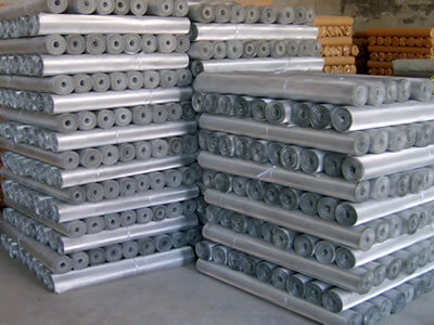 Many rolls of packaged galvanized steel window screen pile up in order.