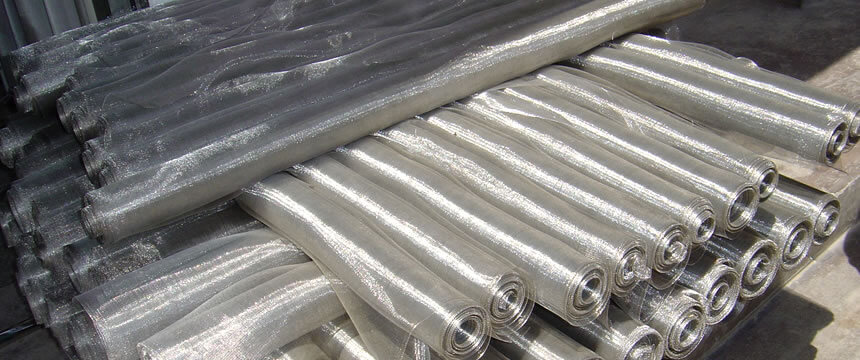 Many rolls of stainless steel window screen pile up.
